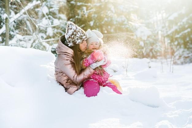 Mãe e filha embrulhadas em um lenço em uma floresta de inverno nevado. viagens e recreação