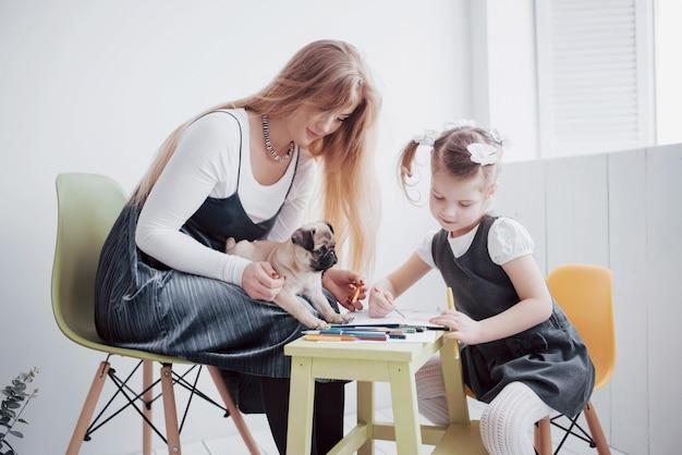 Mãe e filha empates estão envolvidos na criatividade no jardim de infância. pequeno pug com eles