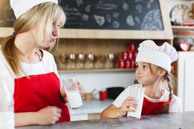 Mãe e filha encantadora se divertir bebendo leite na mesa em uma cozinha aconchegante