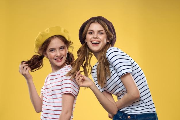 Mãe e filha engraçadas usando chapéus, moda, diversão, alegria, família, parede amarela
