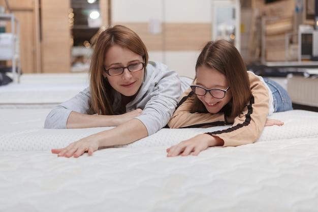 Mãe e filha escolhendo uma nova cama ortopédica para comprar na loja de móveis