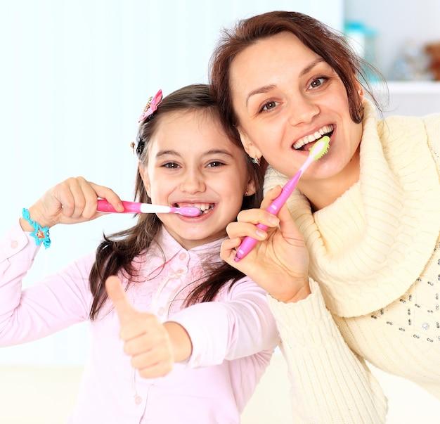 Mãe e filha escovam os dentes.