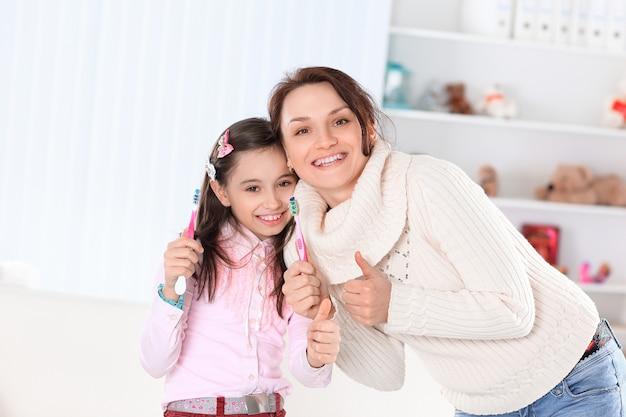 Mãe e filha escovando os dentes. foto com espaço de cópia.