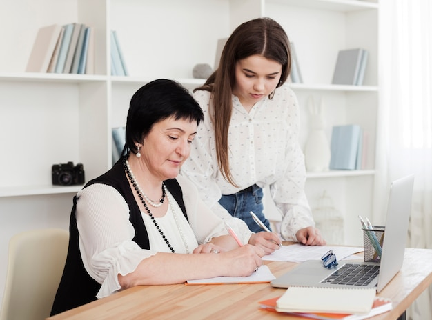 Mãe e filha escrevendo e usando um laptop