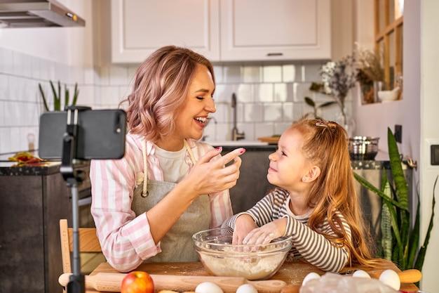 Mãe e filha estão amassando a massa e sorrindo enquanto a preparam para assar, na cozinha leve de casa