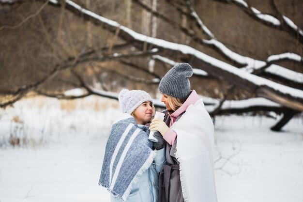 Mãe e filha estão andando na floresta de inverno, embrulhadas em um cobertor, chá ou uma bebida de uma garrafa térmica
