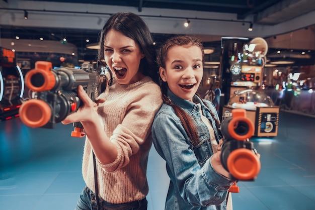 Mãe e filha estão atirando armas no arcade.