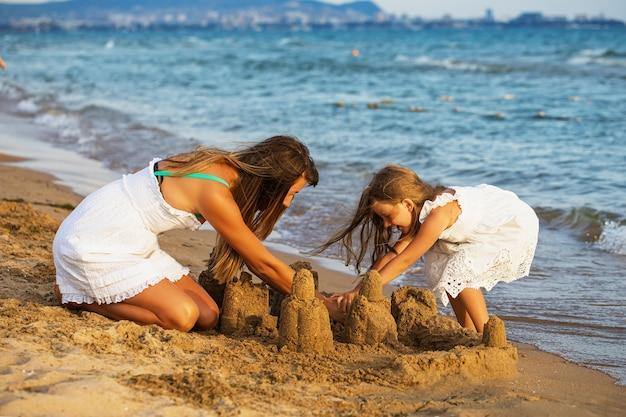 Mãe e filha estão construindo castelos de areia na praia em uma ensolarada noite de verão