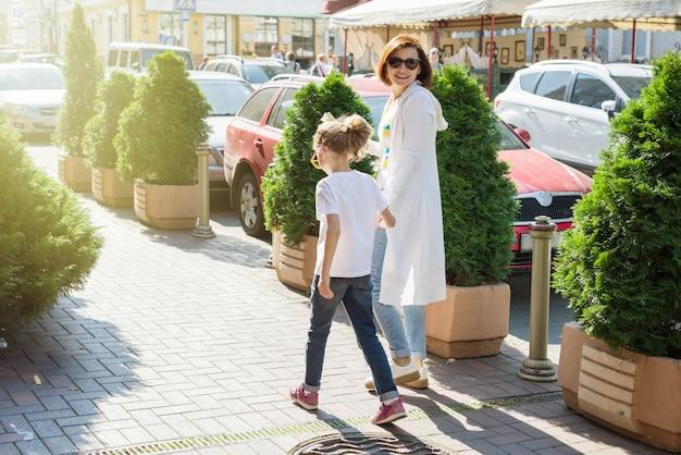 Mãe e filha estão de mãos dadas, caminhando ao longo da cidade