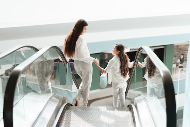 Mãe e filha estão descendo na escada rolante no shopping