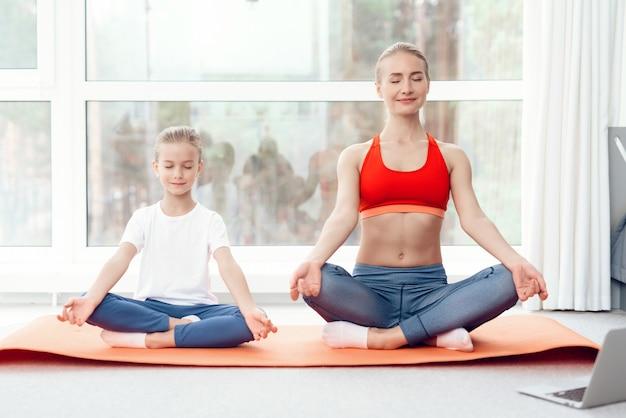 Mãe e filha estão engajados em yoga no sportswear