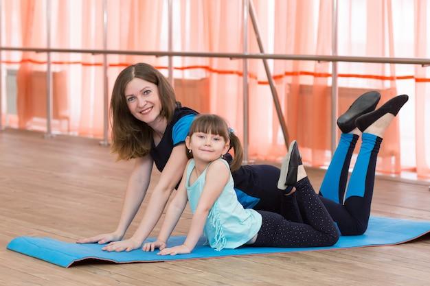 Mãe e filha estão envolvidas em ginástica.