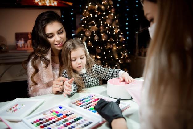Mãe e filha estão escolhendo a cor do esmalte em um salão de beleza antes do natal.