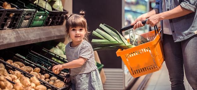 Mãe e filha estão fazendo compras no supermercado