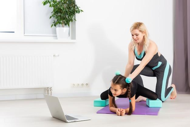 Mãe e filha estão fazendo ginástica no tatame em casa. eles fazem ioga. eles são divertidos porque têm uma família feliz. poses, eles estão olhando para o laptop.