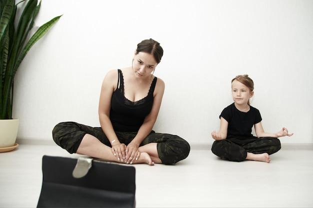 Mãe e filha estão fazendo ioga online