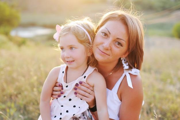 Mãe e filha estão jogando e abraçando no fundo da natureza e o sol poente.