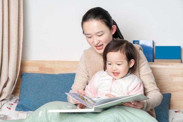 Mãe e filha estão lendo na cama