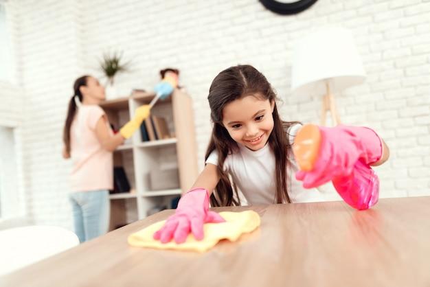 Mãe e filha estão limpando em casa. limpe as prateleiras e a mesa.