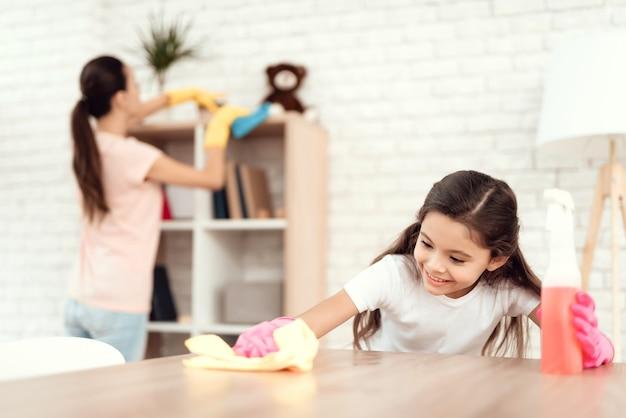 Mãe e filha estão limpando em casa