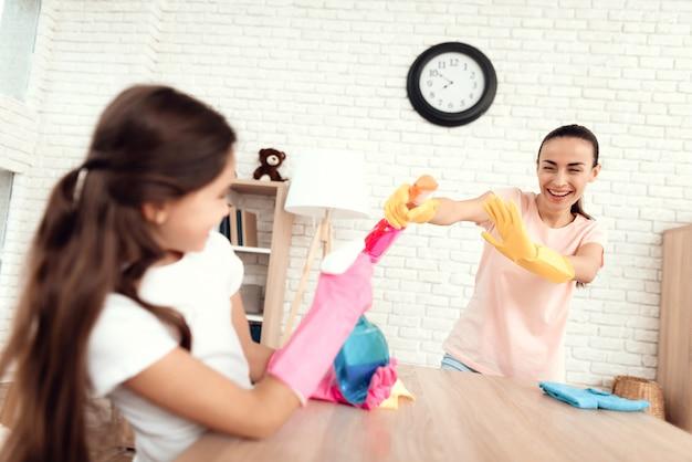 Mãe e filha estão limpando em casa.