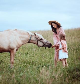 Mãe e filha estão no campo antes de um cavalo