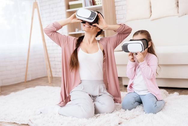 Mãe e filha estão olhando para óculos de realidade virtual.