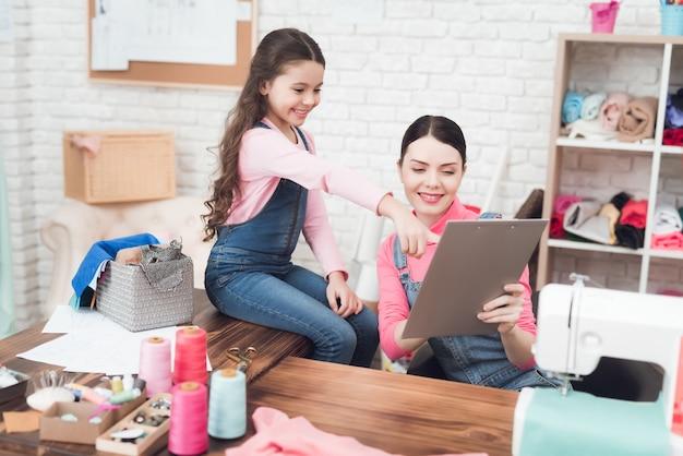 Mãe e filha estão procurando juntos documentos.