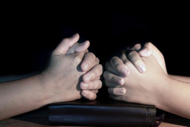 Mãe e filha estão rezando juntos sobre a bíblia sagrada na mesa de madeira com a luz fr