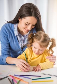 Mãe e filha estão se divertindo enquanto desenha em casa.