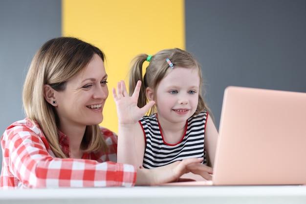 Mãe e filha estão sentadas em frente ao laptop e acenando