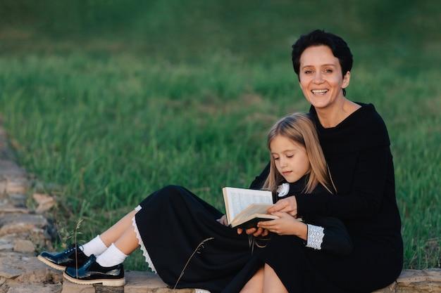 Mãe e filha estão sentadas em um banco de pedra e lendo um livro. mulher com uma criança em vestidos pretos.