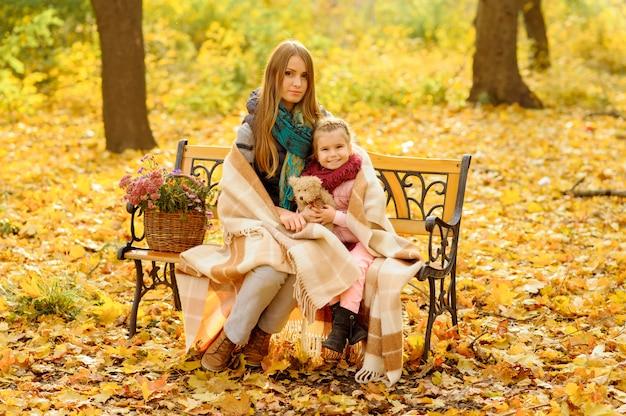 Mãe e filha estão sentadas em um banco no parque outono. uma mulher com uma menininha refugiou-se em um cobertor para se aquecer.