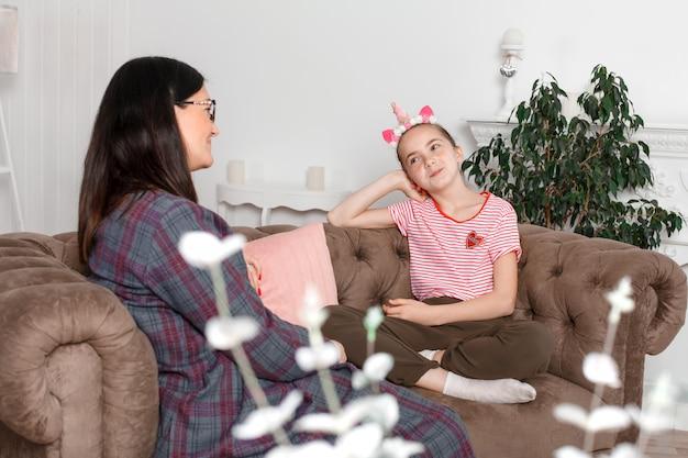 Mãe e filha estão sentadas no sofá e conversando