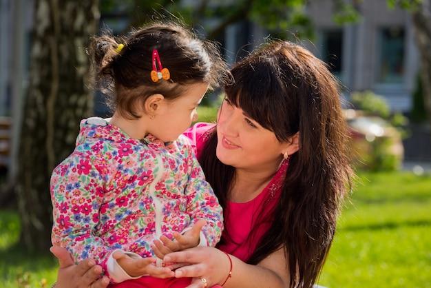 Mãe e filha estão sentados em um banco do parque e olhando um para o outro