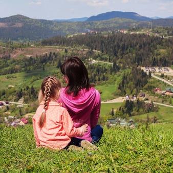 Mãe e filha estão sentados na grama