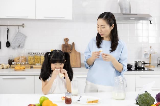 Mãe e filha estão tomando café da manhã na cozinha