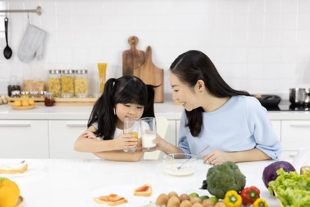 Mãe e filha estão tomando café da manhã