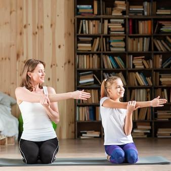 Mãe e filha, esticando os braços no tapete de ioga
