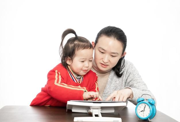 Mãe e filha estudam aula online com computador tablet