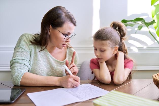 Mãe e filha estudam juntos em casa, sentados à mesa, escreve no caderno. aprendizagem à distância, pais ajudando aluno da escola primária