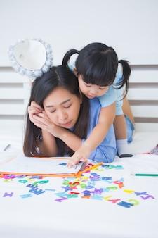 Mãe e filha estudando o alfabeto
