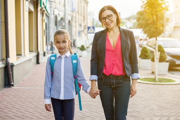 Mãe e filha estudante caminhando para a escola.
