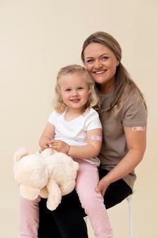 Mãe e filha exibindo adesivo no braço após tomarem a vacina