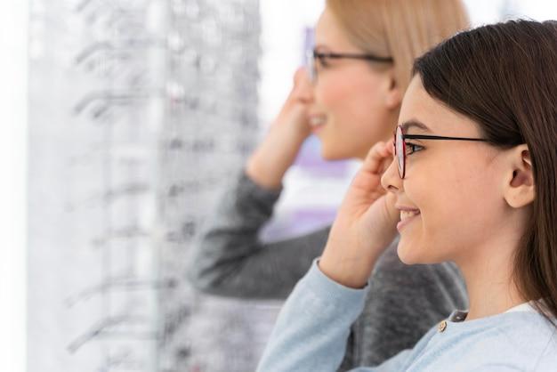Mãe e filha experimentando óculos