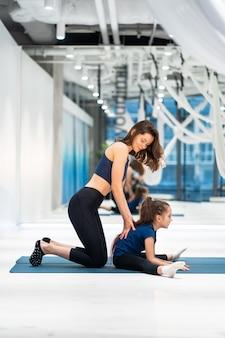 Mãe e filha fazem alongamento antes do exercício