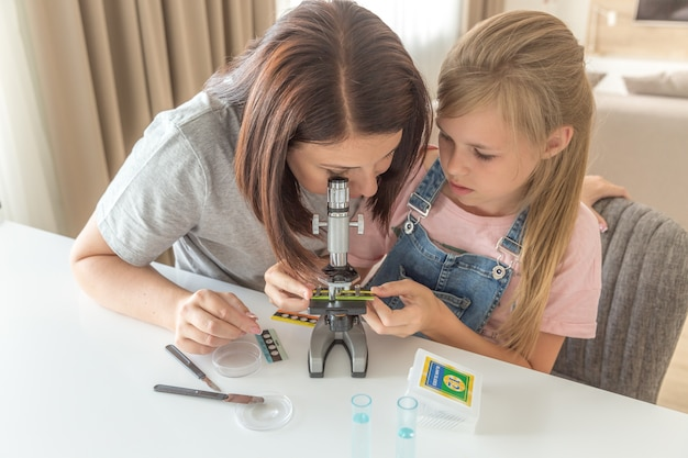 Mãe e filha fazem experimentos químicos com microscópio em casa