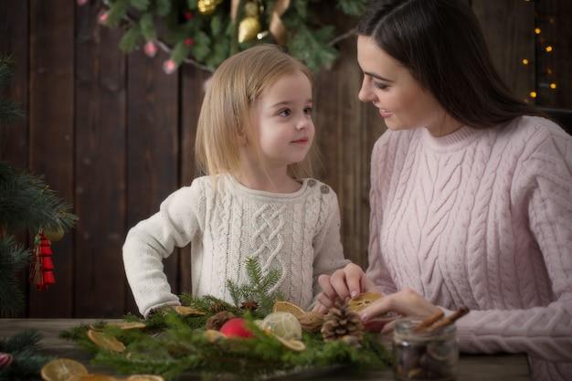 Mãe e filha fazem guirlanda de natal