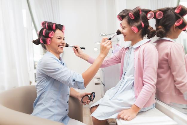 Mãe e filha fazem maquiagem para o outro.