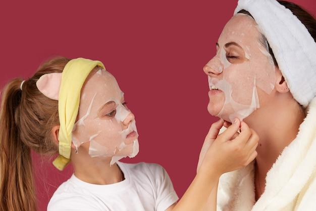 Mãe e filha fazem máscara facial de tecido, cuidados com a pele da família em vermelho isolado